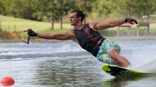 man wearing gloves and black tank top while water skiing